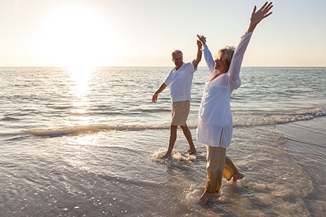 Hombre y mujer maduros paseando por la orilla del mar