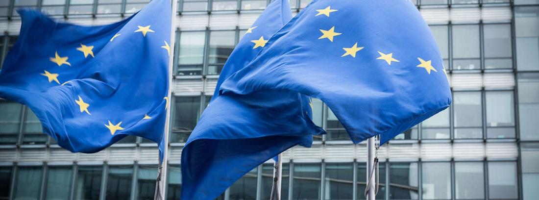 Mazo de juez junto libro de leyes y delante de la bandera europea