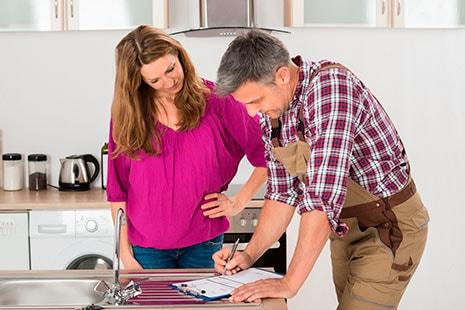 Mujer mira a hombre con peto de trabajo que rellena un papel sobre un fregadero
