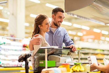 Hombre y mujer pagando en la caja de un supermercado