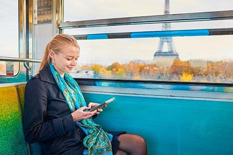 Mujer joven en autobús leyendo con vistas a la Torre Eiffel