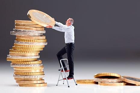 Hombre mayor añadiendo una moneda de euro gigante a una columna de ellas