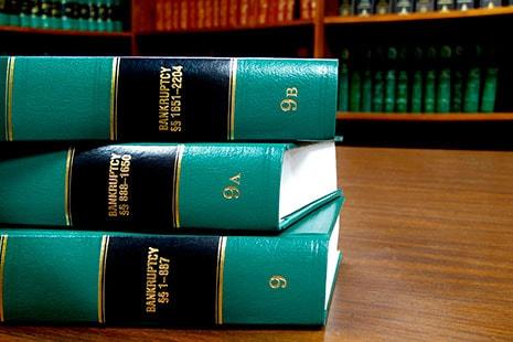 Tres grandes libros apilados y sobre una mesa de madera