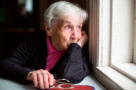 Mujer de avanzada edad mirando por ventana