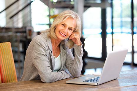 Una mujer mayor sonríe sentada frente a un ordenador portátil