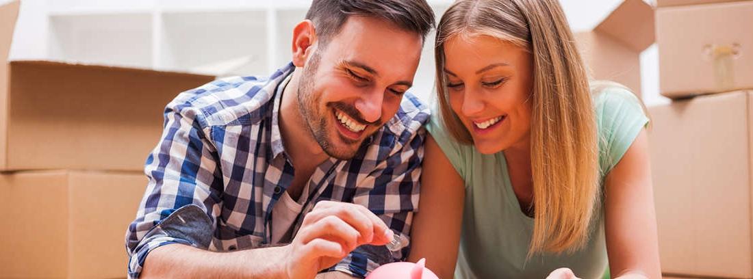 Hombre y mujer jóvenes delante de una hucha, calculadora, papeles y monedas