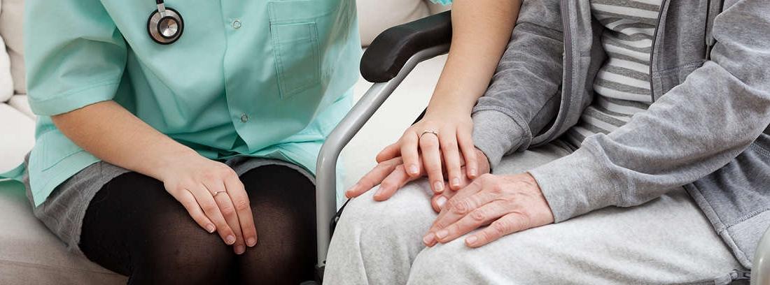 Hombre en silla de ruedas estrecha la mano de mujer sentada en silla de oficina