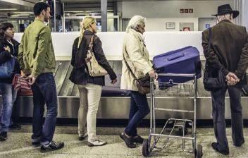 Mujer con maleta de ruedas dirigiéndose hacía control en aeropuerto