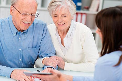 Hombre y mujer en edad de jubilación miran hacia un dispositivo móvil