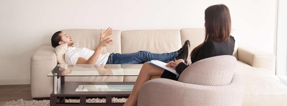 Hombre joven y con gesto pensativo sentado frente a una mujer