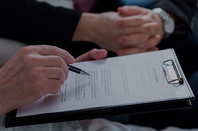 Una mano sujeta un boli sobre unos documentos