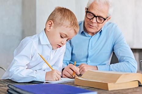 Niño escribiendo mientras le mira hombre mayor también con lápiz en la mano