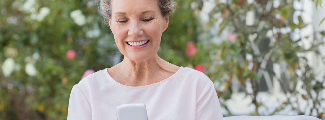 Mano con arrugas sosteniendo un móvil y tocando su pantalla