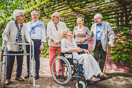 Grupo de personas mayores algunas con andador, bastón y silla de ruedas