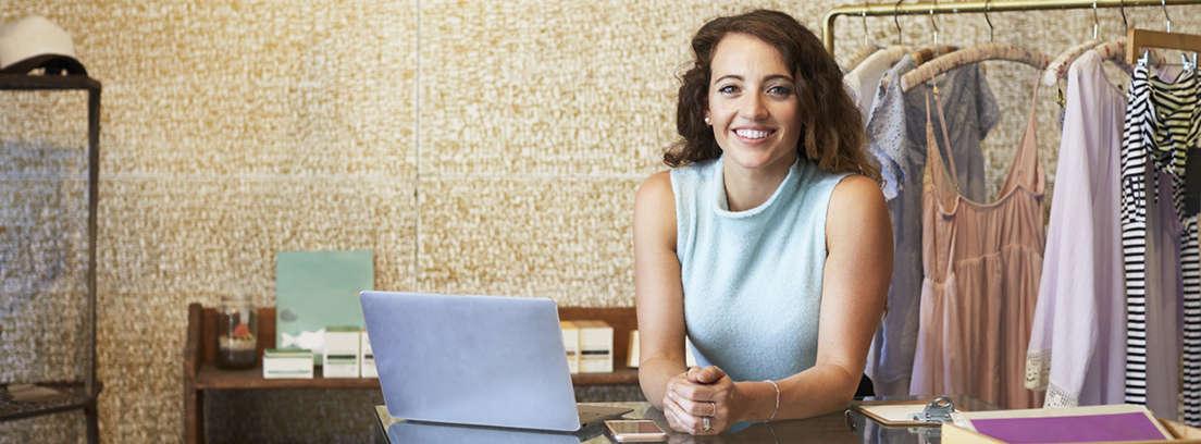 Mujer delante de ordenador con mano sobre barbilla y gesto de duda