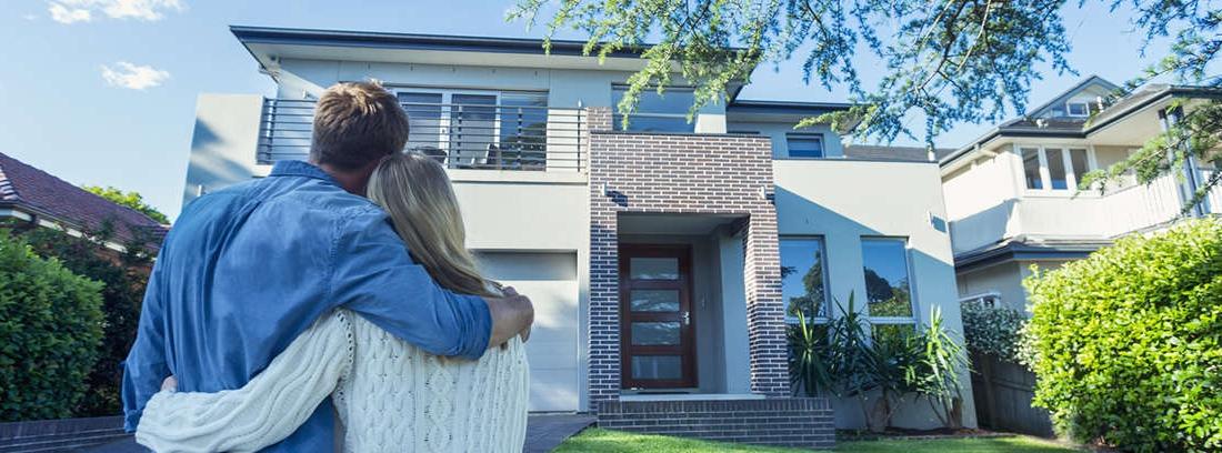 Hombre y mujer de espaldas contemplando la fachada de una casa