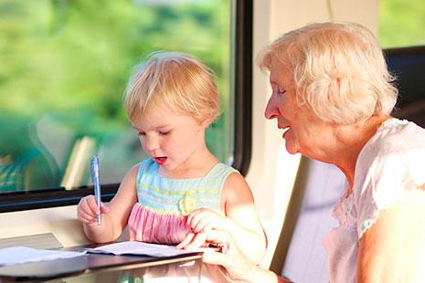 Mujer mayor sentada junto a niña pequeña que sostiene boli sobre un papel.