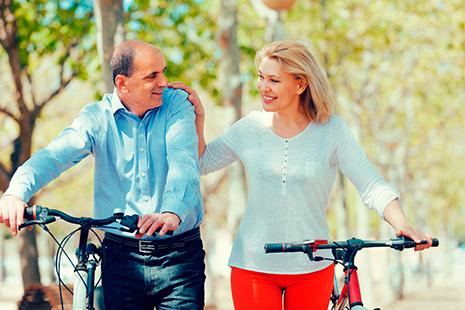Hombre y mujer maduros paseando al lado de sus bicicletas