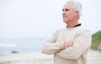 Hombre mayor con brazos cruzados y gesto pensativo