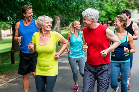 Grupo de hombres y mujeres, mayores y jóvenes corriendo