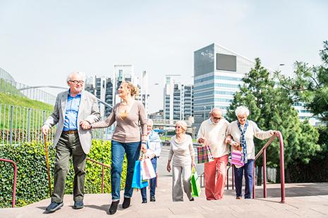 Grupo de hombres y mujeres mayores con bolsas andando por la ciudad