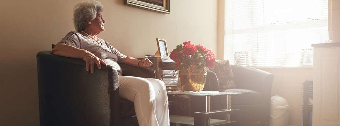 Hombre mayor sentado solo a una gran mesa con gesto triste y preocupado