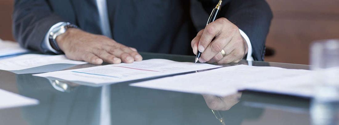 Una mano con un bolígrafo escribe en un papel mientras otra mano señala al mismo.