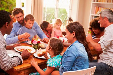 Hombres, mujeres y niños de diferentes edades sentado a la mesa comiendo