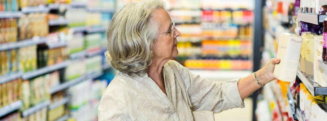 Hombre y mujer mayores delante de un puesto de verduras del mercado