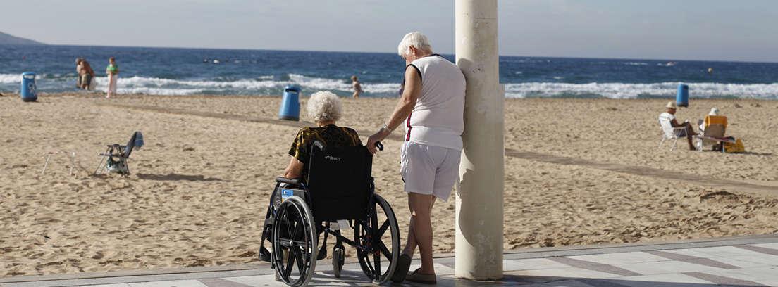 Señal con fondo azul y silla de ruedas junto a pasarela de madera en playa.