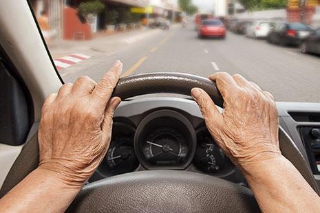 Manos con arrugas sujetando un volante de coche