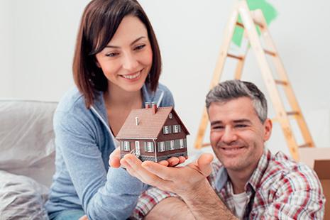 Hombre y mujer con una maqueta de casa en la mano
