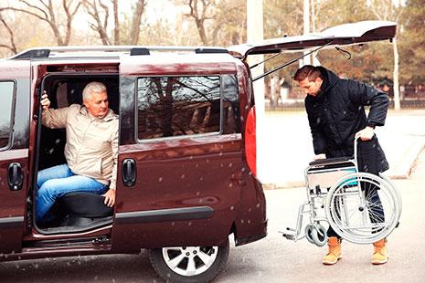 Furgoneta con persona mayor dentro y hombre joven sacando silla de ruedas