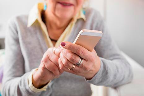 Manos de mujer mayor sujetando un teléfono móvil