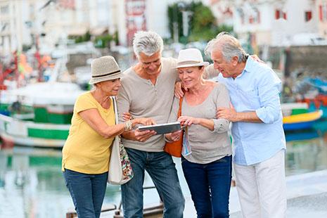 Grupos de dos hombres y dos mujeres mayores mirando una tableta en un puerto