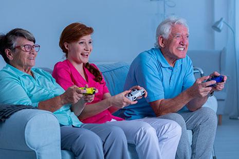 Dos personas mayores y una mujer joven con mandos de consolas sentados en un sillón