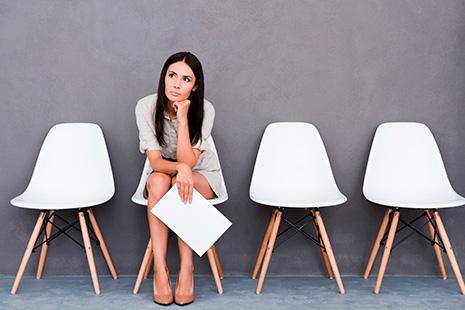 Mujer joven con gesto pensativo sentada junto a sillas vacías  y con papeles en la  mano