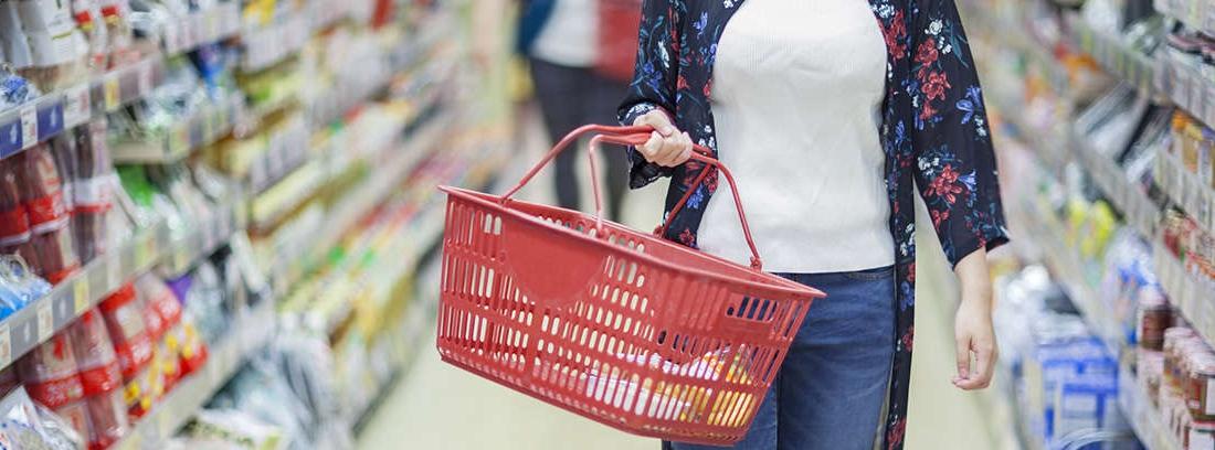 Mujer mayor recoge bolsa con compra que le ofrece un joven en la puerta de casa