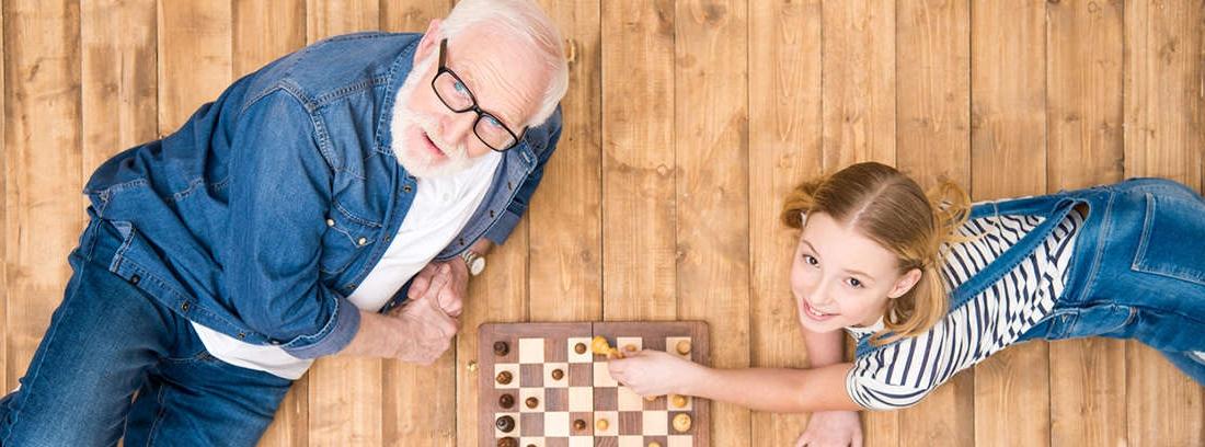 Hombre mayor junto coge por el hombro a joven sentado frente a ordenador