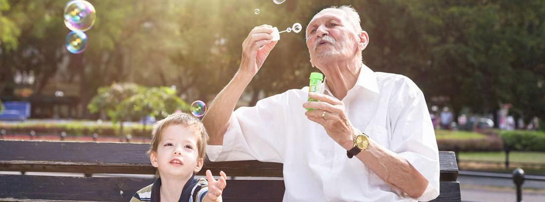 Niño y hombre mayor sentados en banco parque
