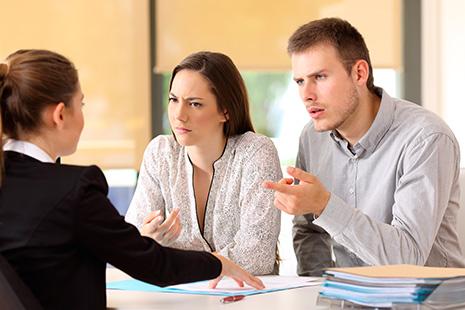 Hombre y mujer sentados frente a otra mujer con gestos de enfado y desagrado