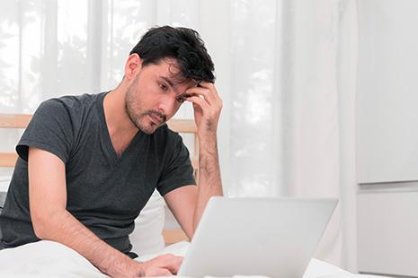 Hombre joven y pensativo delante de pantalla de ordenador portátil