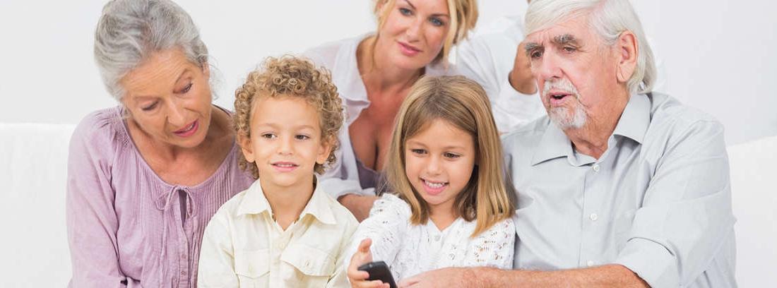 Señora mayor con bol de comida y niña con mando de tele, rodeados de familia y sentados en el sofá