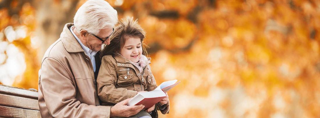 Hombre mayor sonriente con niño alegre en brazos y con un libro entre sus manos