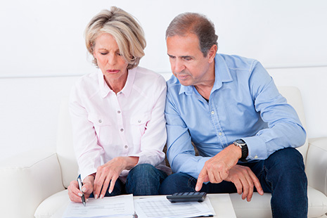 Hombre y mujer maduros sentados delante de una mesa baja con papeles y calculadora