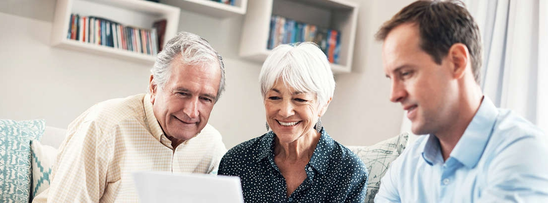 Hombre mayor le tiende la mano a una joven sentada junto a otra