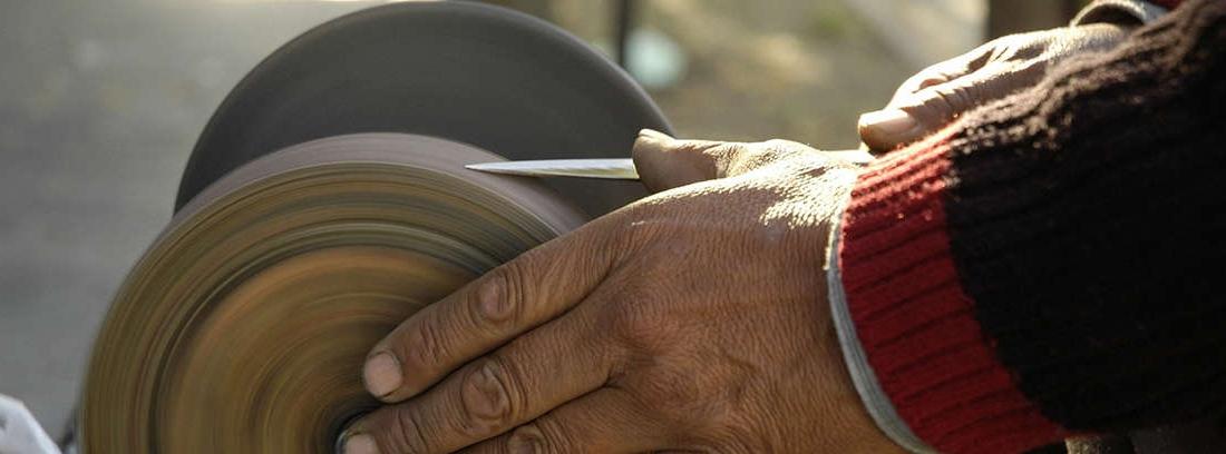 Mano sujetando cuchillo sobre rueda de acero de afilar