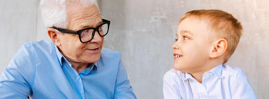Hombre mayor con pesas en una cinta de andar sonríe y otro hombre joven con bata blanca le mira