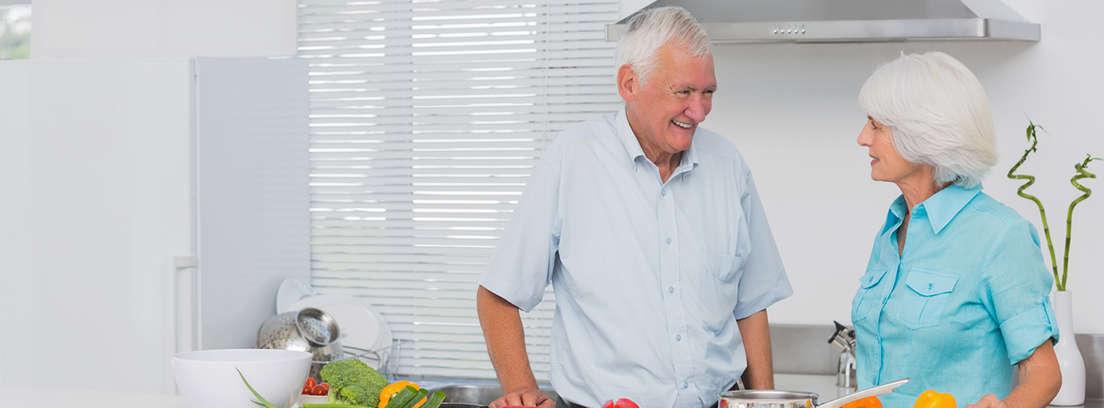 Grupo de hombres y mujeres mayores sonrientes con un móvil y entorno mesa con tazas