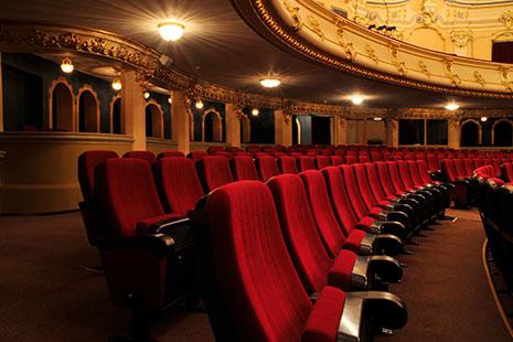 Vista parcial de butacas rojas de teatro, escenario y palcos